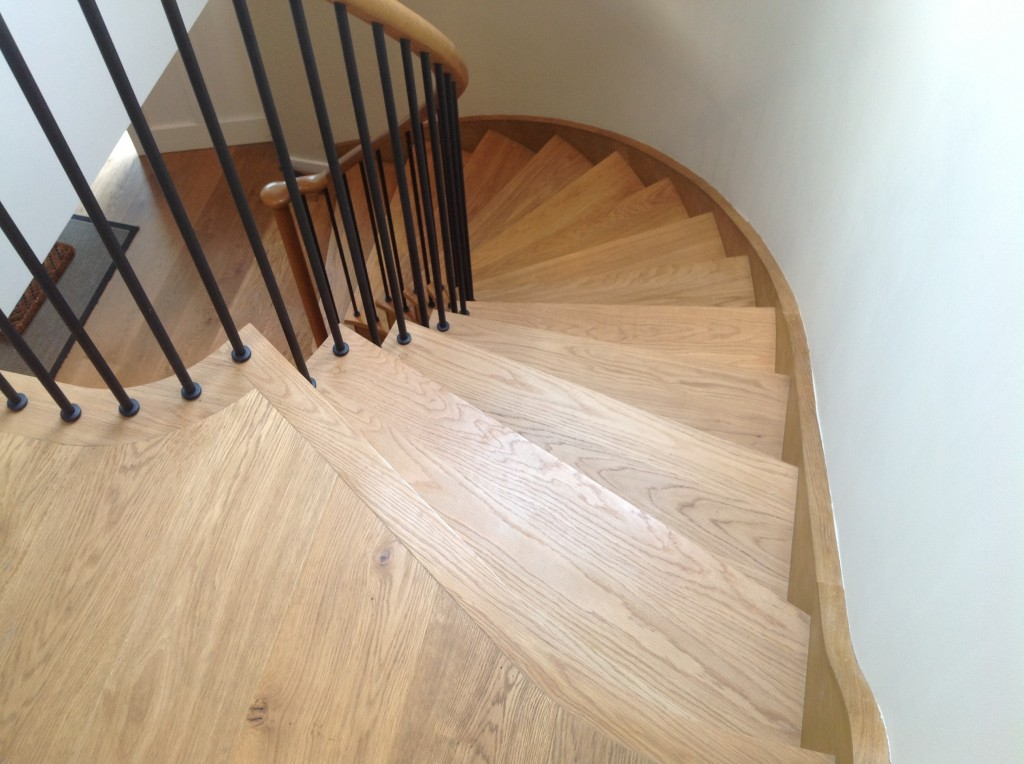 Curved oak stairs with wrought iron spindles