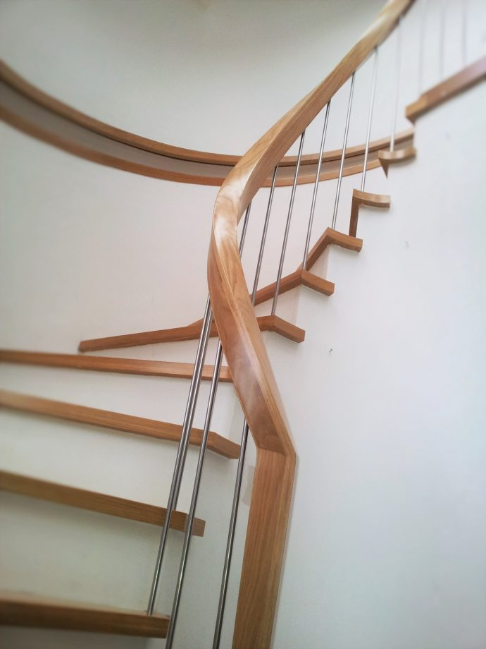 Modern sweeping stairs UK with handrail built into the wall