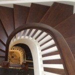 Dark wood stairs with curve with painted spindles
